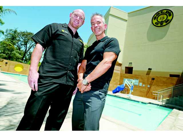 General Manager Brandon Goldstein (left) and President and CEO Angel Banos, Jr. stand next to the new 25-meter outdoor pool at Gold's Gym.