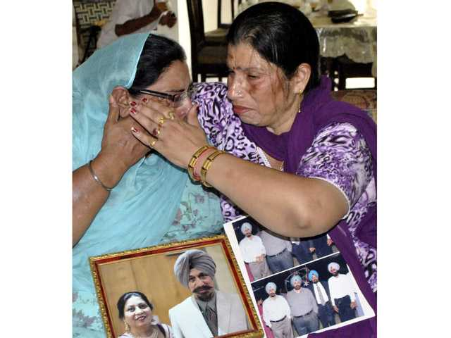 Harinder Kaur Rakhra, left, sister of Satwant Singh Kaleka who was killed in the shooting attack at a Sikh temple in the U.S. state of Wisconsin, is consoled by Seema Sharma, a local politician in Patiala, India, Monday.
