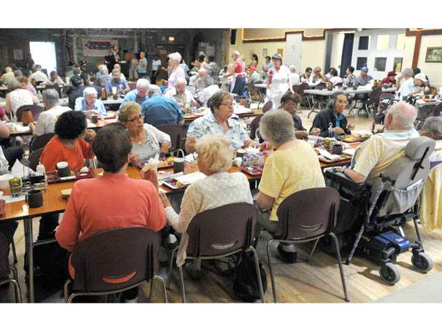 People eat lunch in the dining room at the Senior Center.