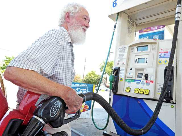 Leland Davis, of Valencia, fills up his car's gas tank at the Arco station on Newhall Avenue in Newhall on Tuesday.