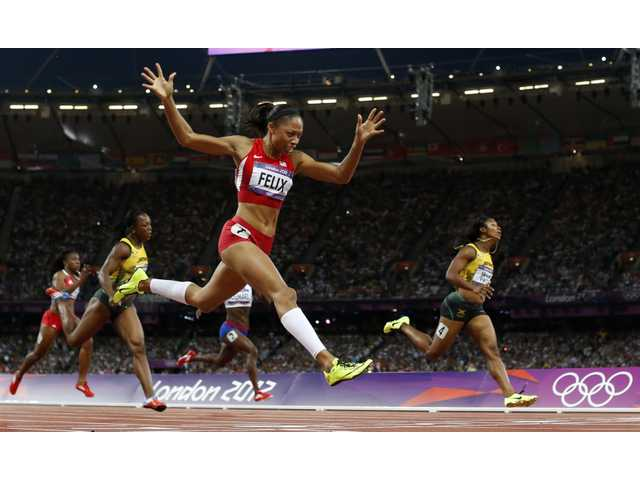 United States runner and Santa Clarita resident Allyson Felix, second from right, crosses the finish line to win gold in the women's 200-meter final on Wednesday in London.