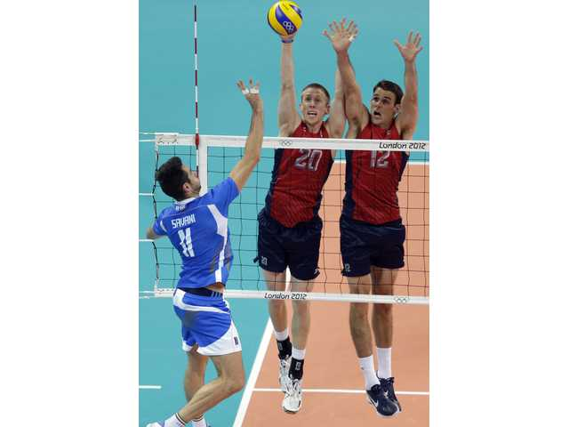 Italy's Cristian Savani (11) drops a shot over USA player and Saugus High alum David Smith (20) and Russell Holmes (12) during a men's volleyball quarterfinal match on Wednesday in London.