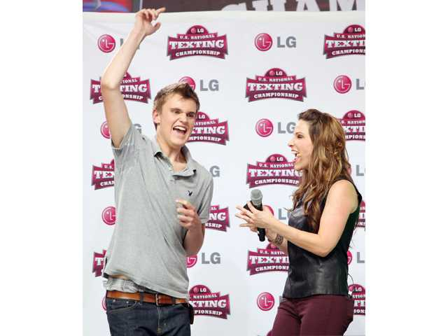 Austin Wiershcke, of Rhinelander, Wis., left, celebrates after winning the LG U.S. National Texting Championship for the second year in a row Wednesday, in New York's Times Square.