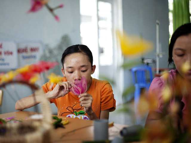 Ho Thi Lang, 18, left, and Pham Thi Thuy Linh, 21, learn how to make artificial flowers on Aug. 7 at the supporting center for victims of Agent Orange in Danang, Vietnam.  The U.S. will begin cleaning up leftover dioxin that was stored at the former military base.