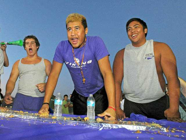Valencia football player Jay Jay Wilson, center, indicates that he finished his portion of his team's burrito.