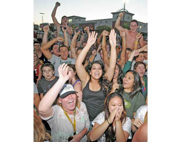 Canyon High football fans cheer as the team finishes its burrito.