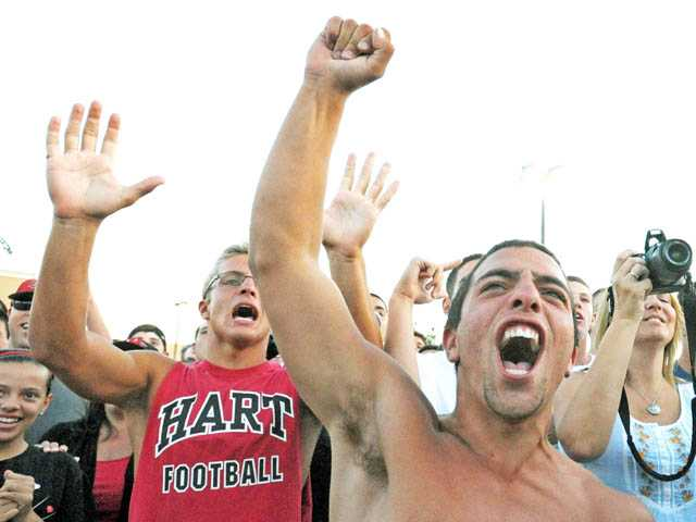 Anthony Caso, right, cheers, as the Hart High team competes at the third annual Burrito Bowl outside Dick's Sporting Goods in Santa Clarita on Thursday.