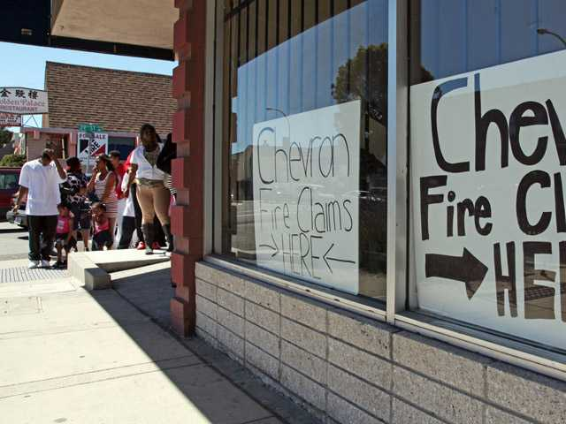Area residents line up outside the injury attorney offices of R. Nicholas Haney in Richmond, Calif., on Tuesday, to pick up a claim form in response to the Chevron refinery fire that impacted the community.