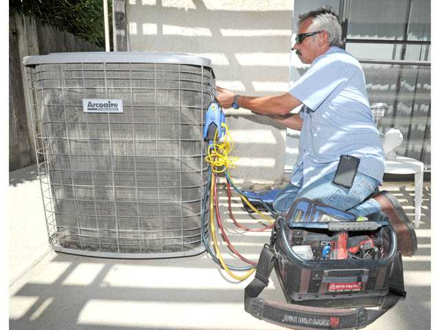 Bob Lucas works on an air conditioner behind a home in Newhall on Friday.
