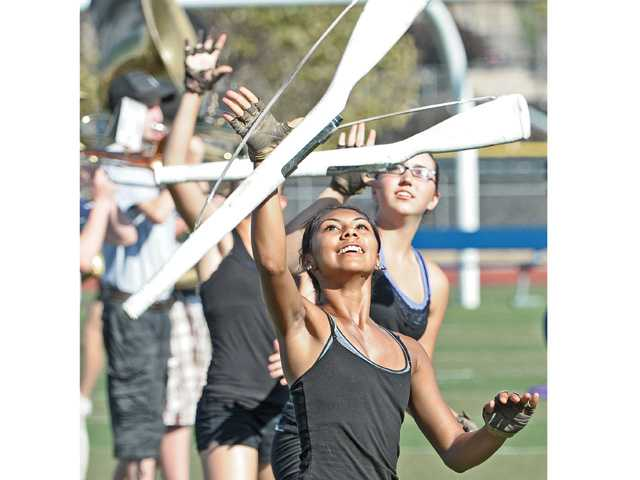 Rosario Palomino, center, and Lauren Pate of the Saugus High School color guard toss rifles in a performance at the campus on Friday.