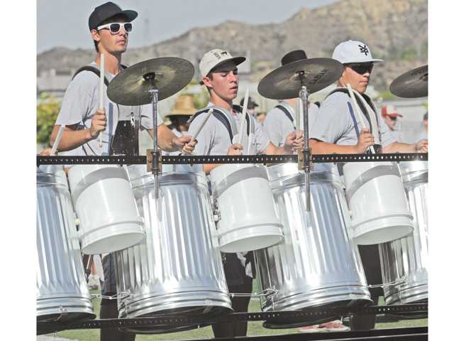 "From left, Jeff Broderick, Evan Hildbrand, and Ricardo Astiazaran drum on ""the trash rack"" as they perform to a routine of Beatles music for friends and family on the Saugus High School football field on Friday."