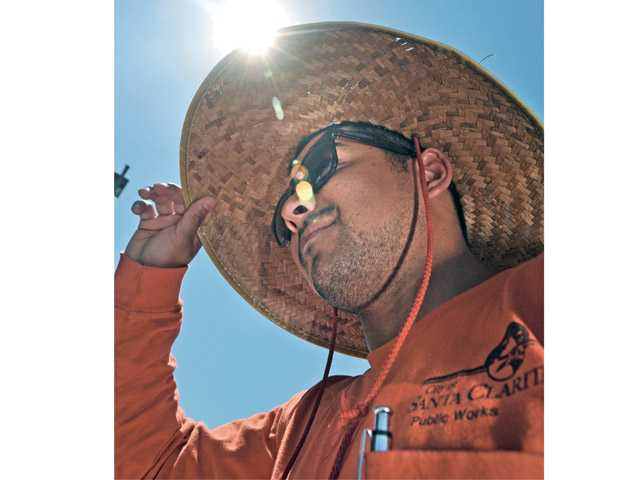 Santa Clarita worker Peter Arreola shields himself while working in the heat on Friday.