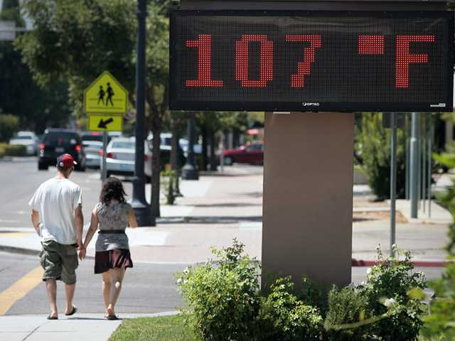 The sign at the Clovis Memorial District building reads 107 degrees, Friday, in Clovis, Calif. Both Friday and Saturday the extreme heat hitting the Central Valley will be closing in on records.