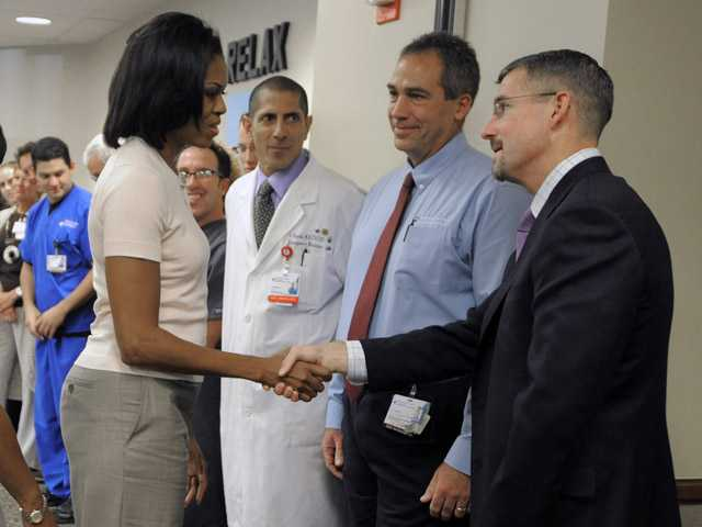 First lady Michelle Obama shakes hands with Dr. James Denton, a first responder to the Aurora theater shooting, at The Medical Center of Aurora on Saturday in Aurora, Colo.