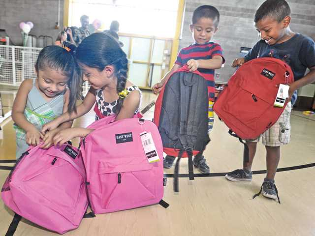 From left, Daniela Berdou, 3, and sister Yoselin, 6, examine their new school supplies as brother Abner, 5, and friend Edy Us, 5,  check out their new backpacks at the Back to School Festival and backpack giveaway held at the Newhall Community Center on Saturday.