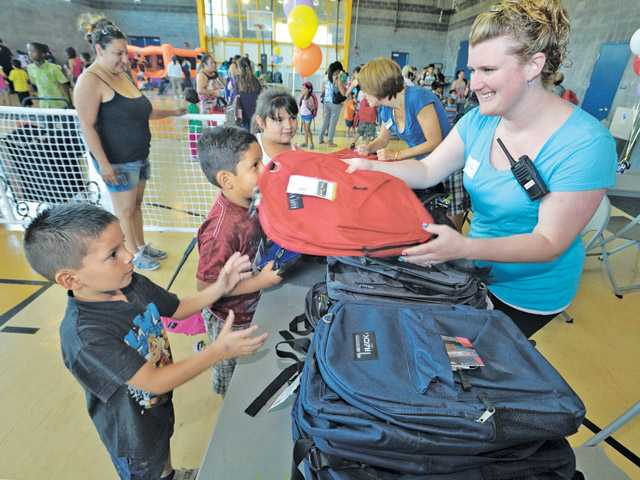 Dominick Sanchez, 5, left, gets a backpack from Krystal Reyes, director of Bringing Learning And Service Together at the Back to School Festival at the Newhall Community Center on Saturday.