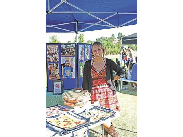 Amanda Keating poses next to handmade Haitian crafts that she was selling at Central Park in Saugus on Sunday.