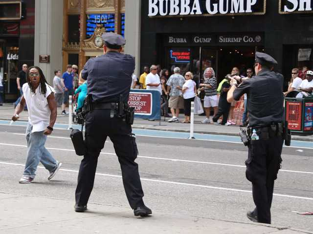 In this Saturday photo, police and a man wielding an 11-inch knife confront each other in New York's Times Square.