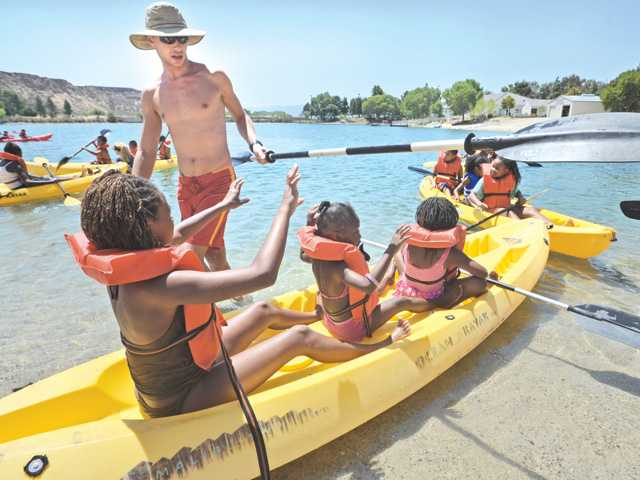 CSUN lifeguard Paul Jacobson hands over the oar to one of the of the 80 summer campers from the 109th Street Recreation Center and Watts Community Center in Los Angeles as they attend the boating instruction and water safety program at Castaic Lake in Castaic on Saturday.