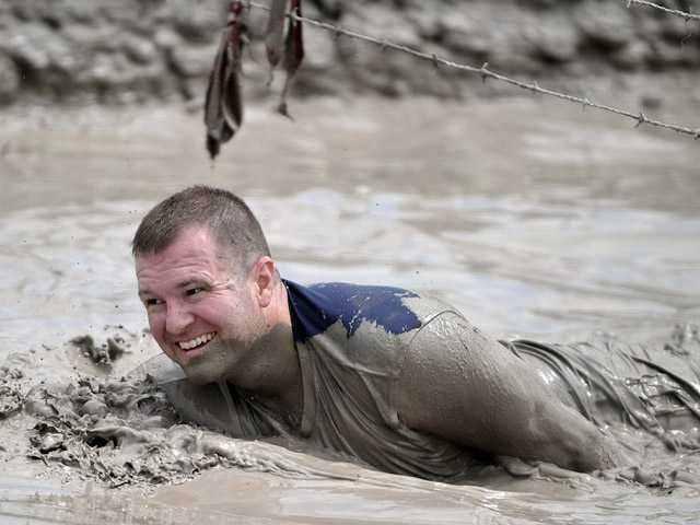 In this June 17 photo, Jeffrey Boehmer makes his way through the Muddy Mayhem obstacle at the Warrior Dash at Pocono Raceway in Long Pond, Pa.