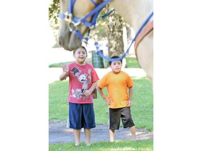 Nine-year-olds Eddie Chutan, left, and Kevin Guzman wave to the unit's horses near a lunch gathering of a North Hollywood church group.