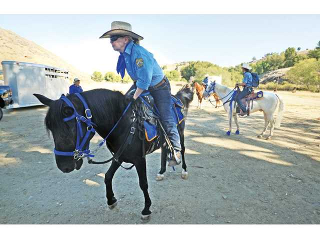 North County Mounted Patrol Assistance Unit member Kimberly Dwight mounts a horse to patrol Castaic Lake on Thursday.