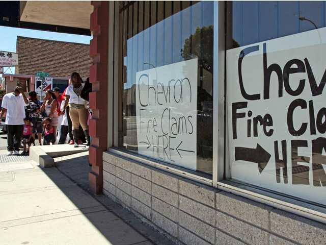 Area residents line up outside the injury attorney offices of R. Nicholas Haney in Richmond on Tuesday, Aug. 7, to pick up a claim form in response to the Chevron refinery fire that impacted the community.