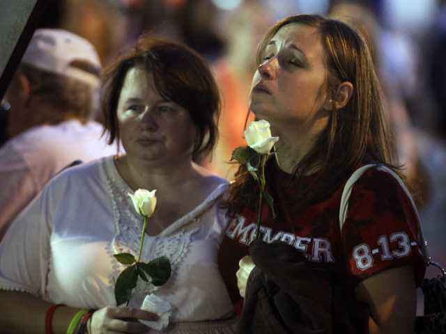 Tamiko Schaefer, of Melbourne, Fla., right, and Lacey Grabek, of Noblesville, Ind., reflect during a moment of silence for the seven people killed and dozens injured when stage rigging collapsed at the Indiana State Fair in Indianapolis a year ago on Monday.