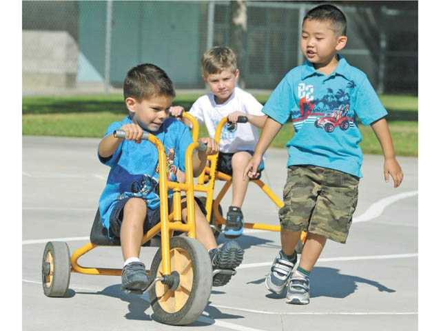 From left, transitional kindergarten students Zachary Post, Grayson Gonzales and Dylan Tran play during recess on their first day at Castaic Elementary School on Monday.