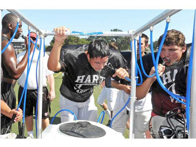 Hart High School football players cool off during practice on the Newhall campus on Monday afternoon. If the Weather Service forecasts prove accurate, the current heat wave could break 2003 record of 12 consecutive days of weather 100 degrees or hotter.