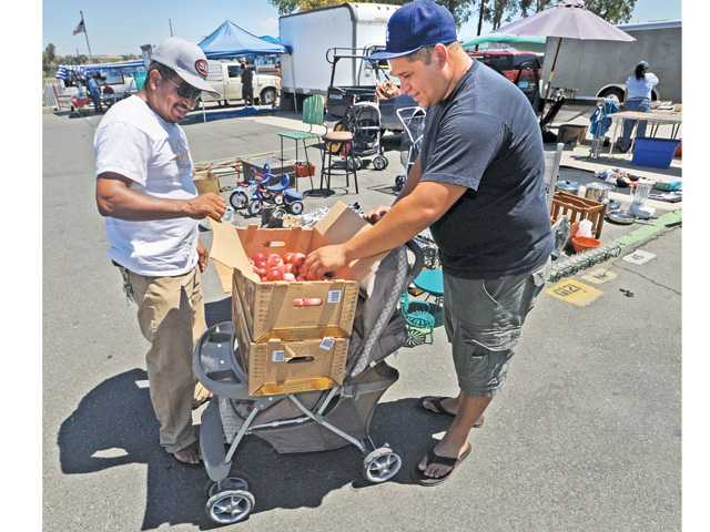 Swap meet vendor Sergio Garcia, left, and fruit vendor Alex Segura of Seguar Produce bicker over the price of two cases of nectarines sitting on a baby stroller as the more than 80 vendors fold up shop early due to the heat at the Tuesday Swap Meet held at the Saugus Speedway in Saugus on Tuesday .