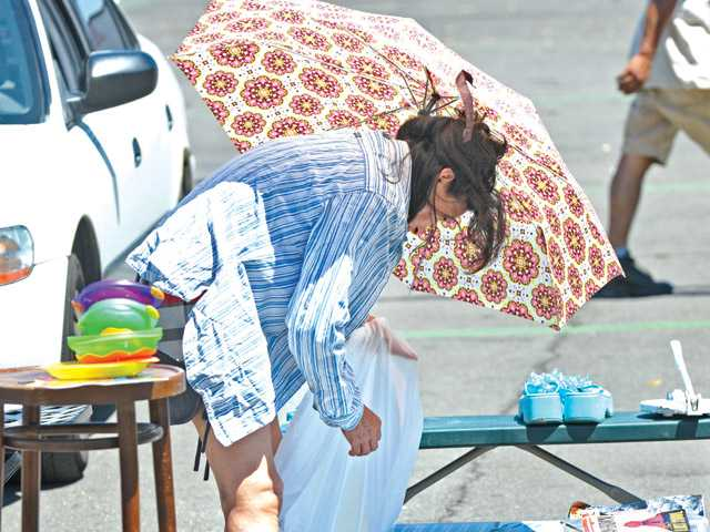 Swap meet vendor Leticia Vasquez packs up early due to the heat under the shade of her umberella at the Tuesday Swap Meet at Saugus Speedway in Saugus on Tuesday.