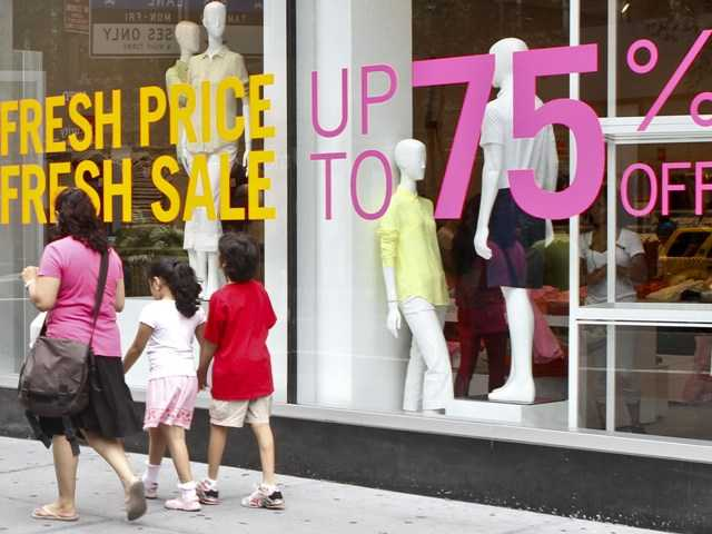 In this July 19, 2012 photo, shoppers in New York pass signs for discounted clothing sales. U.S. retail sales rose in July by the largest amount in five months, buoyed by more spending on autos, furniture and clothing.