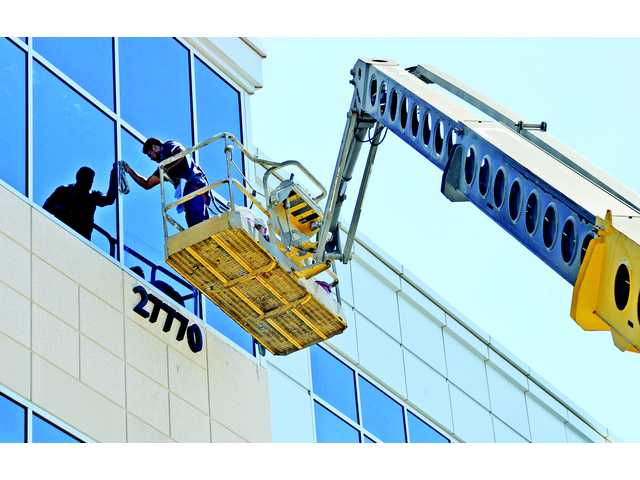 Window washer Hector Zabala of HSG, Inc. cleans a window panel of the LNR Entrada Gateway Center in Valencia on Wednesday.