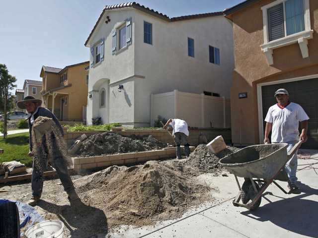 Builders work on a house in Pardee Homes' Crestview area in Santa Clarita.
