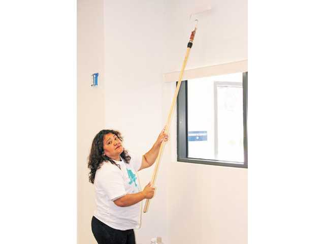 Elejida Campos paints the ceiling.