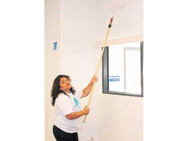 Elejida Campos paints the ceiling.