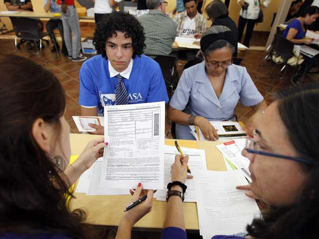 Immigrants Daniel Nino, left, with his mother Patricia Cara from Colombia, get help with documents and filling with the Deferred Action Childhood Arrivals applications at Casa de Maryland in Langley Park, Md., on Wednesday.