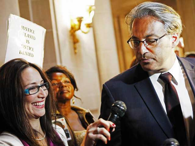 San Francisco Sheriff Ross Mirkarimi and his wife Eliana Lopez, left, are surrounded by media during a break in a San Francisco Ethics Commission hearing in San Francisco, Thursday Aug. 16, 2012.