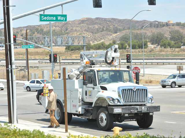 Employees work to restore power in Castaic at the corner of Hasley Canyon Road and The Old Road on Thursday.