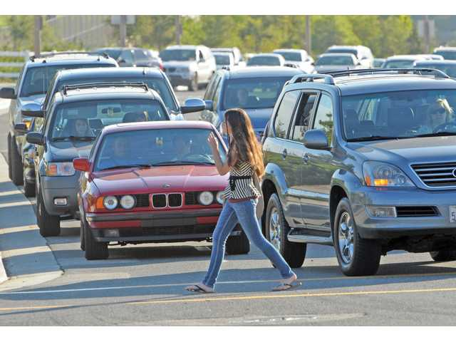 A West Ranch High School student crosses Valencia Boulevard, heading to the first day of school in Stevenson Ranch on Thursday.