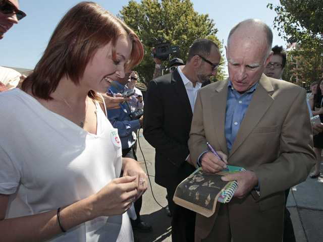 Gov. Jerry Brown autographs a 1978 newspaper clipping of himself for Kelsy Knox, 22, after his kick-off appearance for his November ballot initiative, during his visit to New Technology High School in Sacramento on Wednesday.