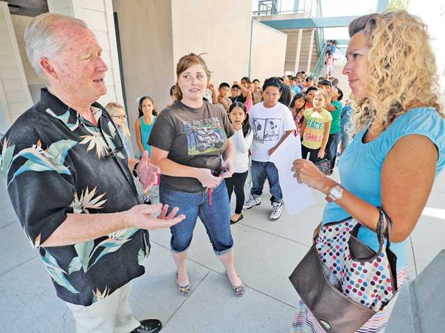 Principal Larry Heath, left, chats with third-grade teachers Kari Madison, and Angela Melizan, right, at McGrath Elementary School in Newhall on Friday.