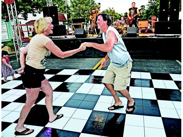 Mary Brunty, left, and Keith Williams dance to the songs of Hard Six at the Senses Rockabilly Street Show held on Main Street in Newhall on Thursday night.