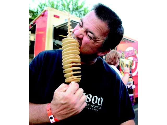 Jim Coffey, of Newhall, takes a bite of his tornado potato offered by a food truck.