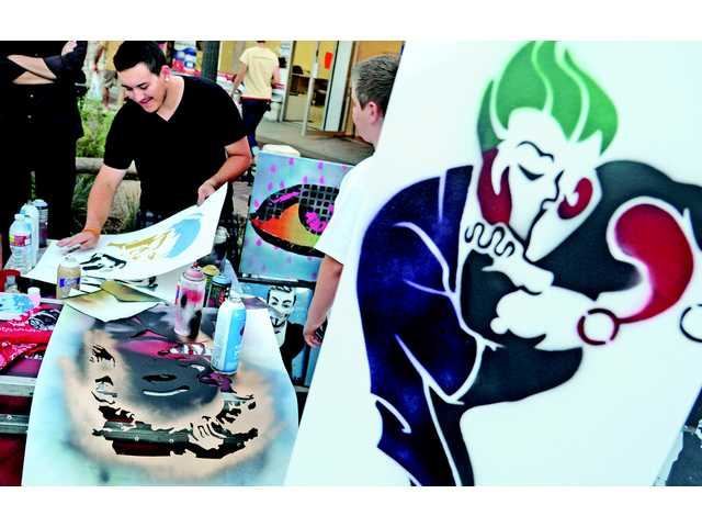 Spray paint artist Ricky Misas demonstrates his stencil art creations.