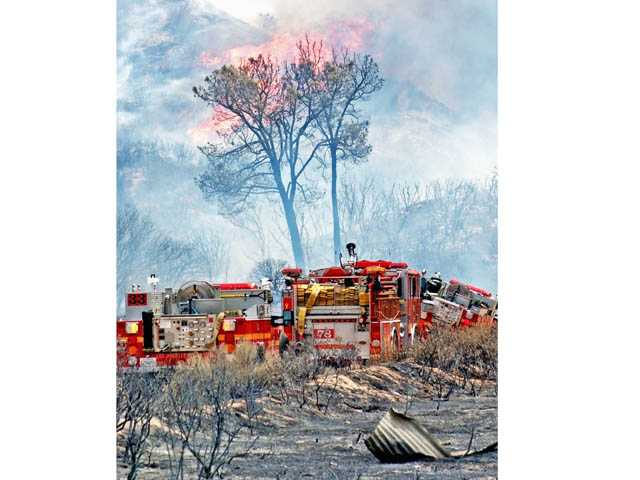 Flames make a run on a hillside above engines as firefighters from Los Angeles County, Kern County and the US Forest Service fight a brush fire east of Interstate 5 in Gorman on Saturday.