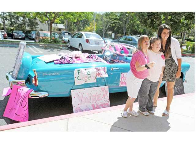 From left, Monica Monheim, Tamara Wilson and Amy Moore pose in front of a Ford Thunderbird with messages and memorabilia for Melissa Grason parked outside Blessed Kateri Tekakwitha Catholic Church in Saugus on Saturday.