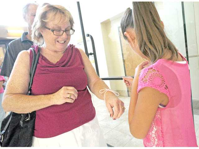 Kaiya Janjuh, 9, right, places a pink piece of string on Linda Adams as friends and family gather.