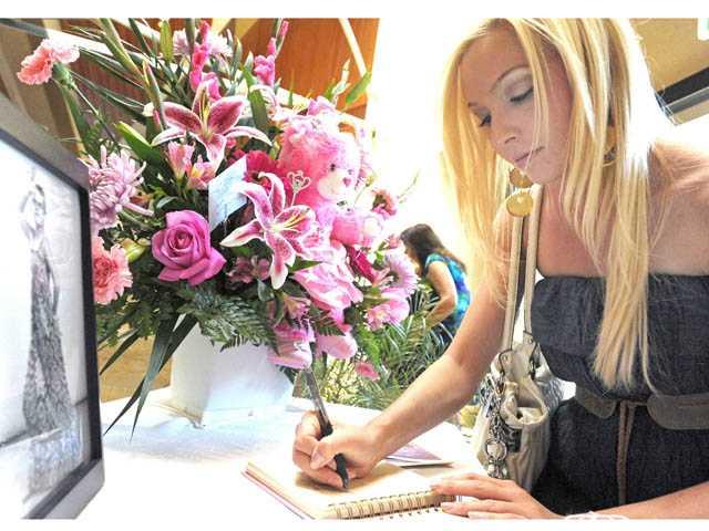 Amanda Larsson-Dally signs a condolence book.